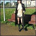 Nackt im Freien im langen Mantel und mit Stiefeln